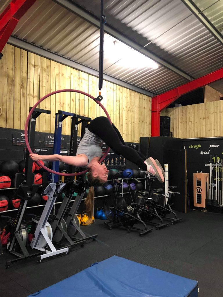 Laura doing shoulder mount on the aerial hoop